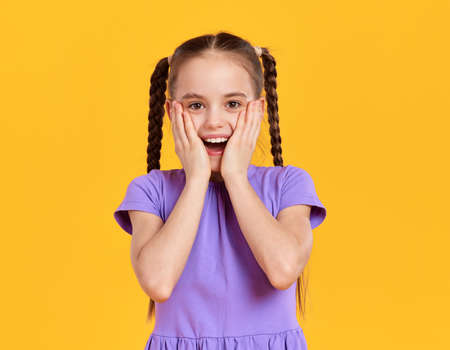 Happy excited little girl with pigtails wearing casual purple dress touching cheeks and looking at camera against yellow background