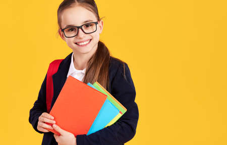 Cute smart girl in glasses smiling and looking at camera with textbook during school studies against yellow background