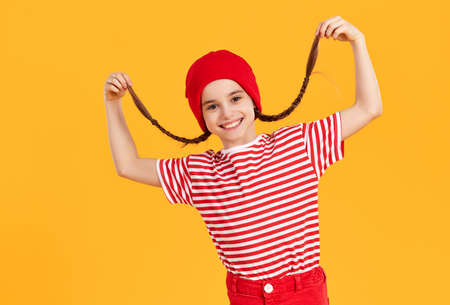 Happy hipster preteen girl wearing red hat and striped shirt laughing merrily and holding on to her pigtails against bright yellow background Foto de archivo