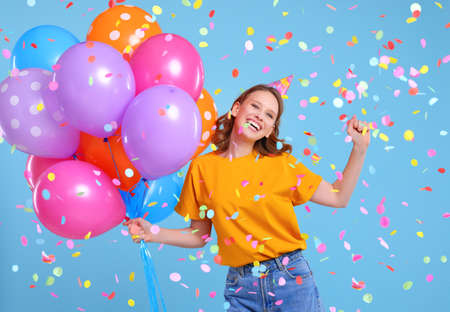 Optimistic woman with colorful balloons smiling and dancing under falling confetti during birthday celebration against blue background Foto de archivo