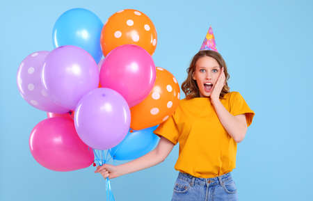 Happy amazed young female in party hat holding bunch of colorful balloons and looking at camera with excitement while standing against blue background