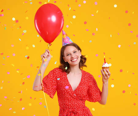Happy young female in party hat with red balloon and cupcake having fun during birthday celebration against yellow background with confetti Foto de archivo