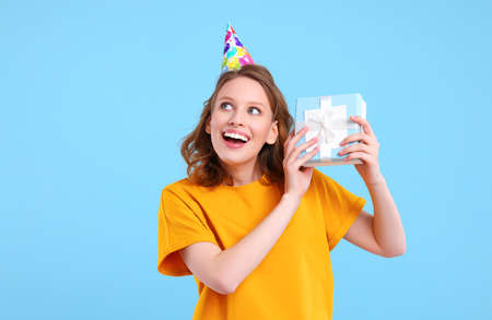 Delighted female in party hat and with present in box standing on light blue background and looking up