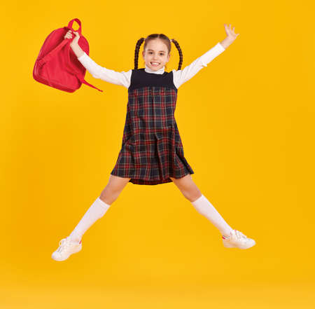 Full length girl in trendy school uniform holding bagpack and jumping against yellow backdrop Foto de archivo