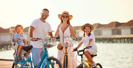 Content cheerful family: happy parents and kids in summer outfits enjoying bicycle trip riding bikes along wooden embankment near sea at sunset