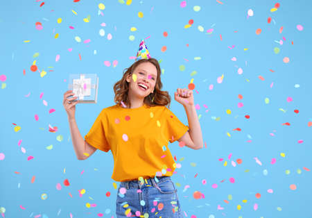 Happy young female in casual clothes and party hat with gift box in hand dancing under colorful confetti during birthday celebration against blue background