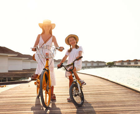 Full body of cheerful family: young woman and little daughter in white summer dresses and hats smiling and looking at camera while riding bicycles on pier near sea