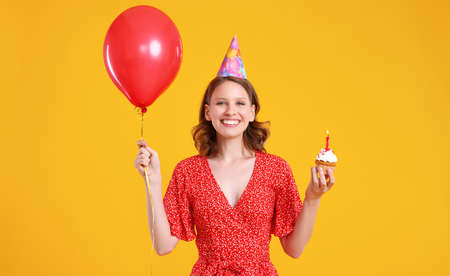 Optimistic female with red balloon and birthday cupcake smiling and looking at camera against blue background