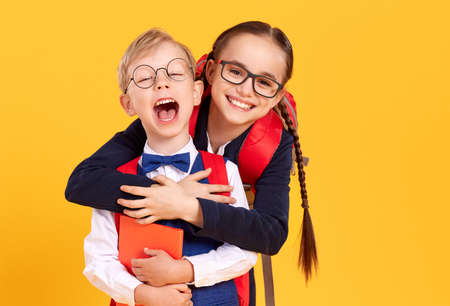 Cheerful girl in school uniform and glasses giving piggyback ride to happy little brother on yellow background