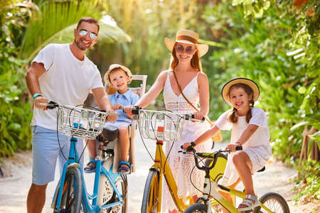 Happy family: parents and kids in summer outfits enjoying bicycle trip in green tropical park during summer holidays together