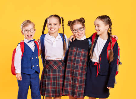 funny happy group children student boy and girls about yellow backdrop Foto de archivo