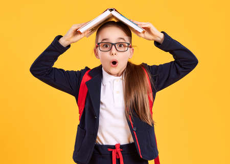 Overwhelmed elementary school student in glasses keeping open textbook over head and looking at camera with astonishment while standing against bright yellow background
