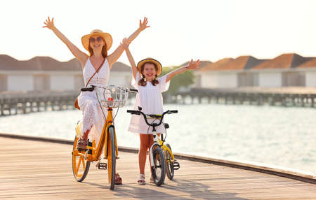 Full body of cheerful young woman and little daughter in white summer dresses and hats raising hands and looking at camera while riding bicycles on pier near sea Foto de archivo