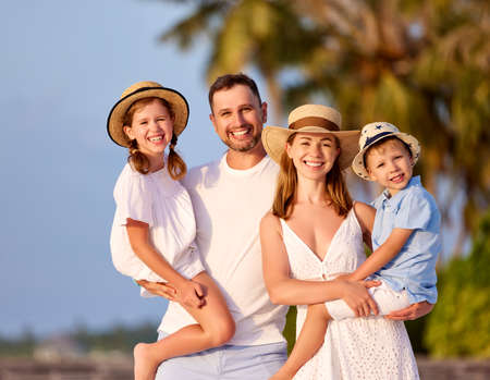 Cheerful family: parents with cute son and daughter smiling happily and looking at camera while spending summer holidays together in countryside