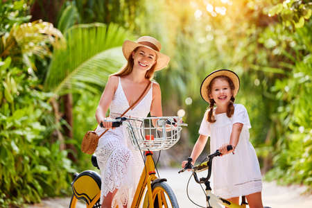 Cheerful young woman with cute little daughter in white dresses and hats smiling and looking at camera while enjoying summer journey and riding bikes in green tropical park Foto de archivo
