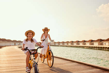 Full body of content cheerful family: woman and little daughter in summer dresses riding bikes along wooden embankment near sea at sunset Foto de archivo
