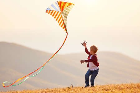 happy kid boy running with a kite at sunset outdoors