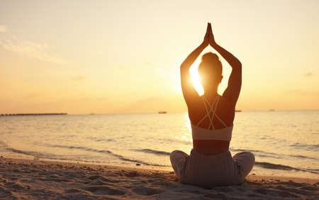 Back view of female sitting in Padmasana while meditating alone on seashore against sky in sundown light Stockfoto