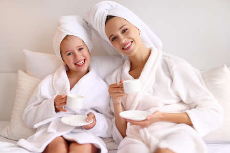 Happy young family mother and daughter in bathrobes and towels smiling and looking at each other while drinking hot beverage in morning on bed