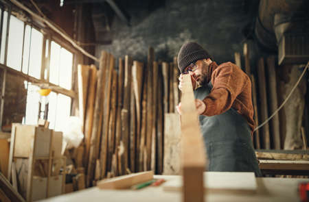 Focused adult male woodworker in apron and knitted gat cutting wooden plank while working in carpentry workshop