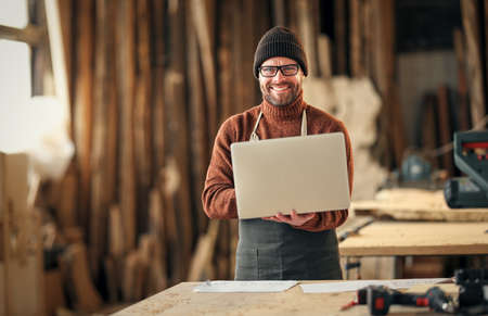 Concentrated adult bearded craftsman with paper in hand checking information on laptop while working in carpentry workshop