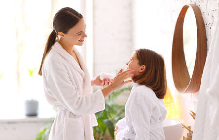 Side view of loving mother applying skincare cream on face of happy daughter while enjoying home spa session together Imagens