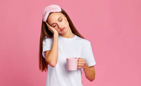 Sleepy young female with closed eyes touching face while drinking coffee early in morning against pink background