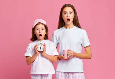 Astonished girl and woman with alarm clock and cup of coffee looking at camera with opened mouth while being late in morning against pink background Imagens
