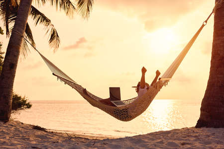 Celebrating success. Full length of excited woman, female freelancer with laptop keeping arms raised while working remotely during summer vacation, lying in hammock on the tropical beach at sunset