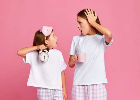 Shocked girl with alarm clock looking at woman with hot drink against pink background in morning