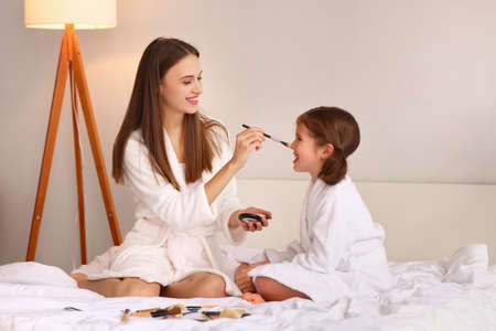 Cheerful young woman in bathrobe smiling and applying powder on nose of delighted girl while resting on bed during skin care routine Imagens