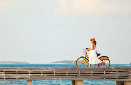 Side view of carefree female in white dress and sunhat walking with bike along wooden embankment near sea at sunset Imagens