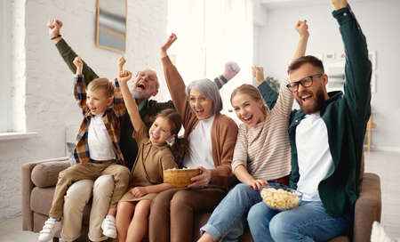 Celebrating goal. Excited big multi generation family, grandparents, young mother and father with little kids sitting on coach in living room and watching football match on tv, having fun together