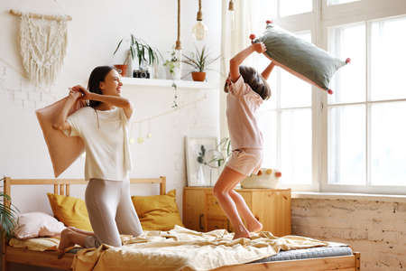 Happy family morning. Full length of overjoyed excited young mother and excited little daughter having pillow battle on bed, two girls older and younger sister laughing having fun in bedroom at home Imagens