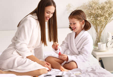 Happy daughter and mother with red nail polish smiling and sitting on bed during hygienic routine in weekend at home