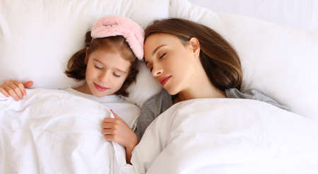 From above young mother and daughter lying on bed under duvet and sleeping in morning at home