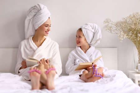 Happy young mother and girl in bathrobes and towels smiling and looking at each other while reading books on bed at home Imagens