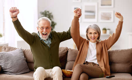 Overjoyed senior couple husband and wife celebrating goal while sitting on sofa in living room and watching football match on tv, happy mature family having fun together while spending weekend at home