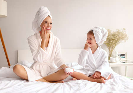 Cheerful mother and daughter smiling while sitting on bed and smearing cream on face during skin care routine at home