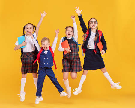 Group of funny excited classmates girls and boy in school outfits with backpacks and copybooks having fun and jumping on yellow background