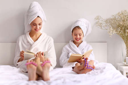 Happy young mother and daughter in bathrobes and towels smiling while reading books on bed at home