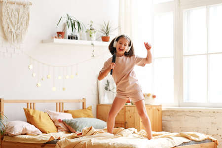 Little star. Cute happy little girl wearing pajama with hairbrush as mic pretending to be famous singer while standing on bed at home, adorable preschool child singing and dancing in bedroom Imagens