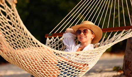 Enjoying summer vacation. Young happy woman wearing straw hat and sunglasses keeping eyes closed and relaxing while lying in the hammock on the sandy beach at sunset. People traveling concept Imagens