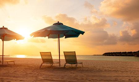 Empty deckchairs under umbrella on sandy beach near calm sea against cloudy sunset sky in summer evening