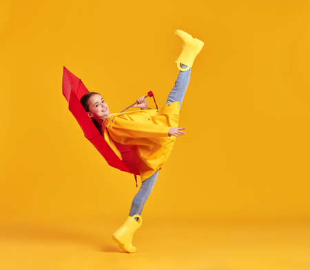 Full body side view of charming little girl in yellow raincoat and gumboots with red umbrella in hand standing with leg raised and looking at camera Imagens