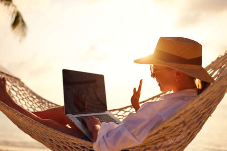 Having online conversation. Young happy successful woman wearing straw hat waving and smiling while having video call on digital laptop, relaxing in the hammock on tropical sandy beach on sunny day
