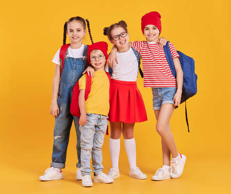 Full body of cheerful school aged girls and boy in colorful casual outfits with backpacks hugging and looking at camera while standing against yellow background