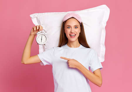 Funny young woman in white t shirt demonstrating alarm clock and looking at camera with happy smile after awakening against pink background Banque d'images