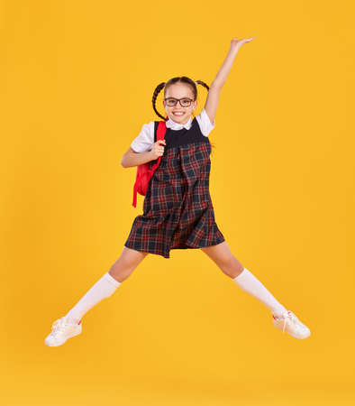 Full body of happy preteen schoolgirl in black uniform and glasses with backpack jumping high against yellow background