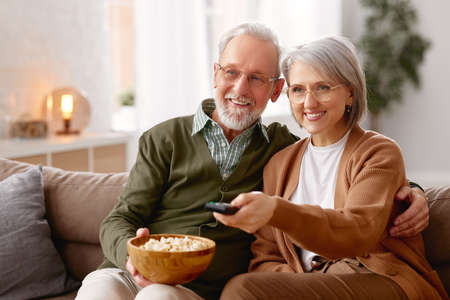Beautiful happy senior couple husband and wife eating popcorn and watching TV while relaxing on sofa in the living room. Smiling mature family cuddling enjoying weekend together. Leisure activities